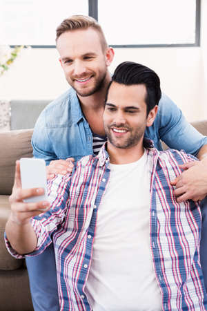 couple on couch: Gay couple relaxing on the couch taking selfie at home in the living room