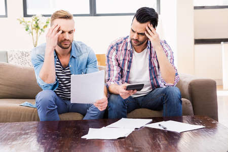 credit crunch: Gay couple worrying about their bills at home in the living room