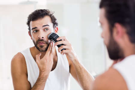 personal grooming: Reflection of concentrated man shaving with electric razor in bathroom LANG_EVOIMAGES