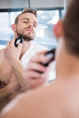 personal grooming: Handsome man shaving in mirror at home in the bathroom