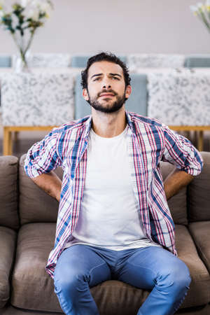 back ache: man with back ache sitting on sofa