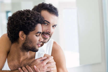 couple bathroom: Happy gay couple hugging in bathroom