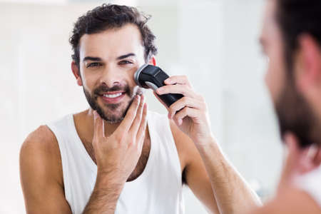 personal grooming: Reflection of smiling man shaving with electric razor in bathroom