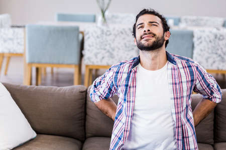 back ache: Man with back ache sitting on sofa LANG_EVOIMAGES