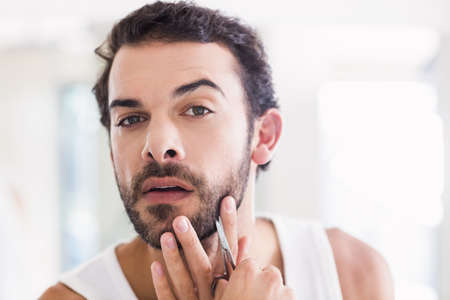personal grooming: Concentrated man cutting his beard with scissors in bathroom