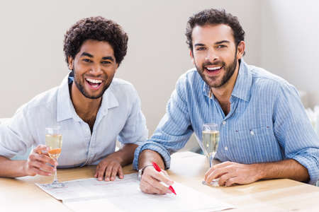 lettings: Happy gay couple drinking champagne and writing on newspaper at home