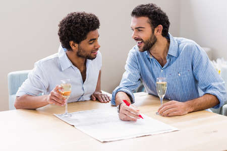 Happy gay couple drinking champagne and writing on newspaper at home