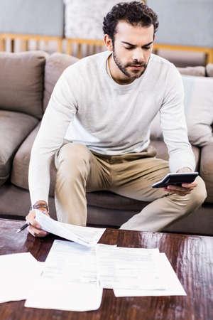paying: Focused man paying bills sitting on sofa