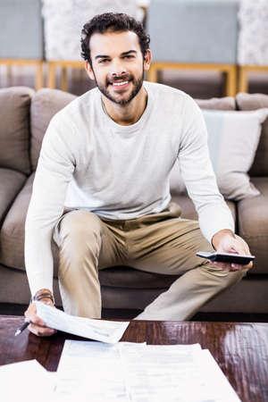 figuring: Smiling man paying bills sitting on sofa