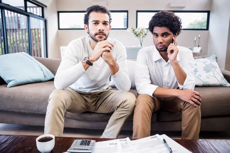 figuring: Worried gay couple with bills on table looking at camera in living room