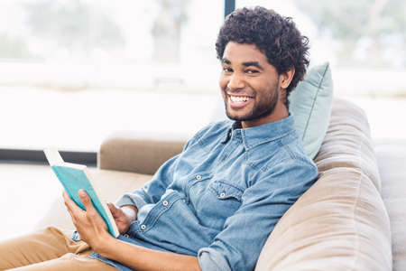 man holding book: Handsome man holding book and smiling at the camera on sofa LANG_EVOIMAGES