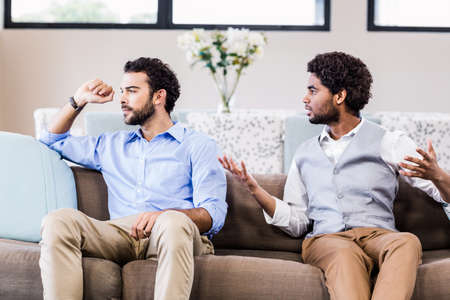 fighting styles: Gay couple arguing on sofa LANG_EVOIMAGES