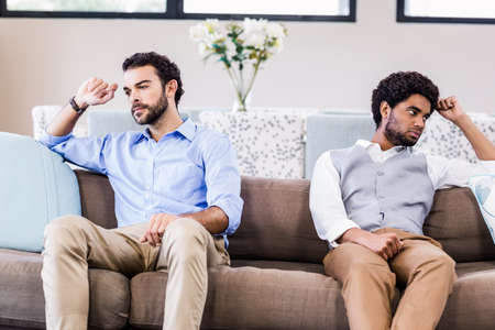 not talking: Gay couple not talking after arguing on sofa