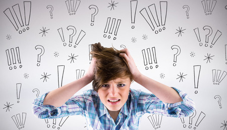 outraged: Pretty brunette getting a headache with hands on head against grey background Stock Photo