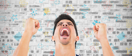 clenching fists: Football player screaming while clenching fists against grey brick wall Stock Photo