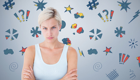 Upset blonde looking at camera with arms crossed  against grey vignette
