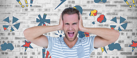 wall covering: Handsome man screaming while covering ears against grey brick wall Stock Photo
