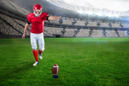 kicking: American football player kicking football against rugby stadium Stock Photo
