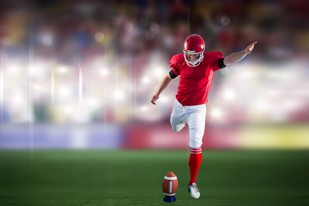 American football player kicking football against sports arena Stock Photo