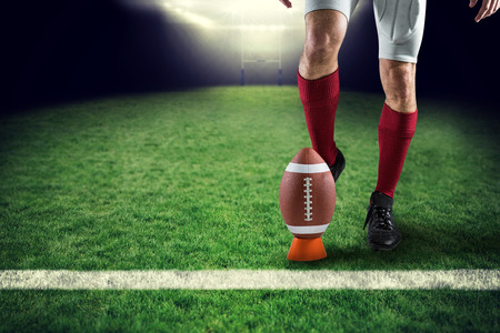 kicking ball: Low section of sports player kicking ball against rugby pitch