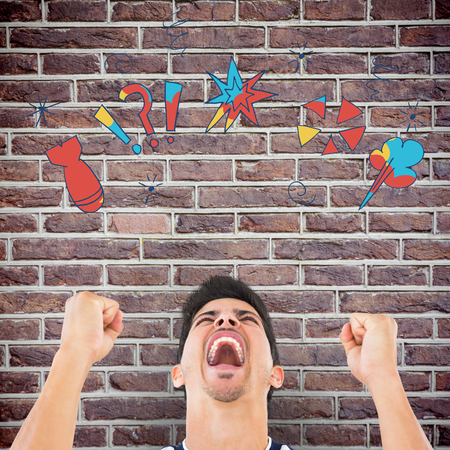 clenching fists: Football player screaming while clenching fists against red brick wall