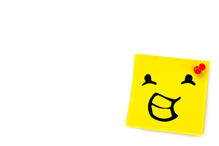 adhesive note: Smiling face against yellow pinned adhesive note