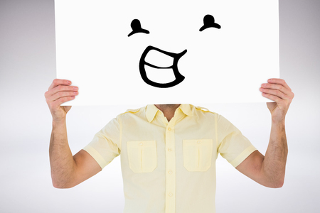 man holding card: Man holding card in front of his face against grey background Stock Photo