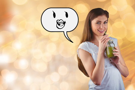 sipping: Pretty woman sipping on green juice against glowing background