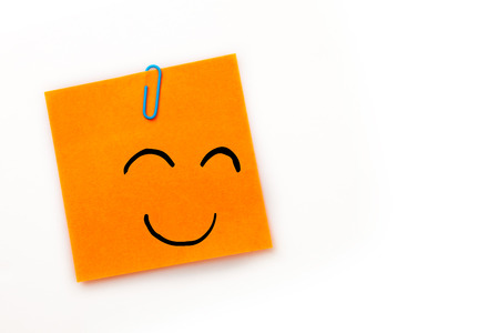 adhesive  note: Smiling face against orange adhesive note with a paperclip