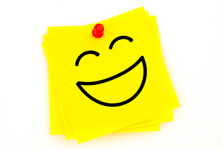 red pushpin: Laughing face against sticky note with red pushpin