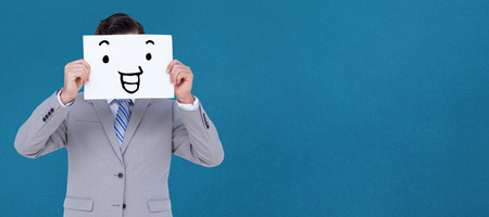 well dressed: Businessman holding blank sign in front of his head against blue background Stock Photo
