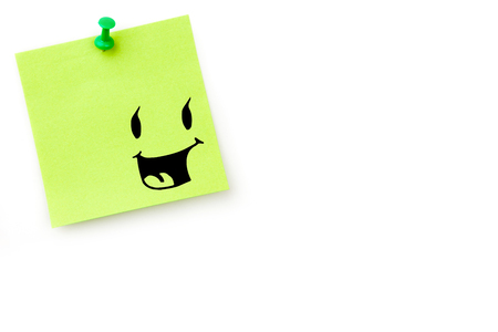 adhesive note: Smiling face against green pinned adhesive note