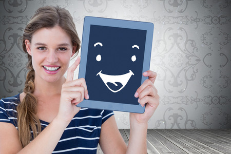 woman tablet: Woman showing tablet pc  against room with grey wallpaper Stock Photo