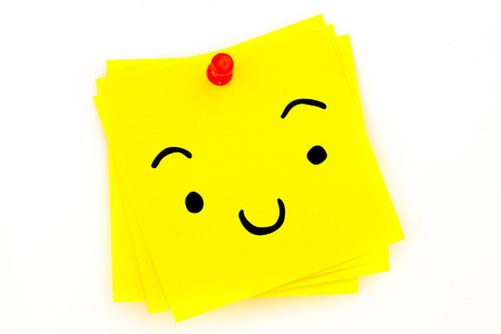red pushpin: Smiling face against sticky note with red pushpin Stock Photo
