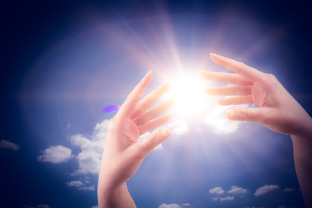 sol radiante: Mano que muestra contra el cielo nublado con sol