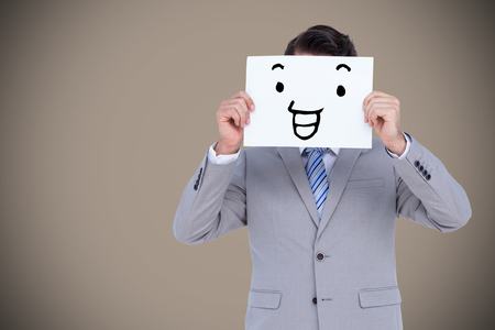 well dressed: Businessman holding blank sign in front of his head against grey background with vignette