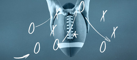 strong strategy: American football player holding up football against blue background