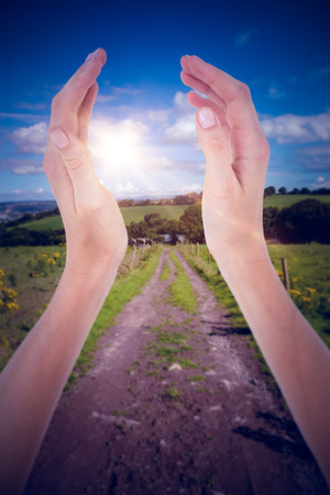 clear path: Woman presenting with her hands against countryside