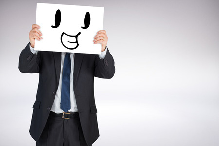 mature adult: Mature businessman showing card against grey background Stock Photo