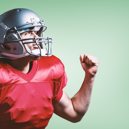 clenched fist: American football player cheering with clenched fist against green vignette Stock Photo