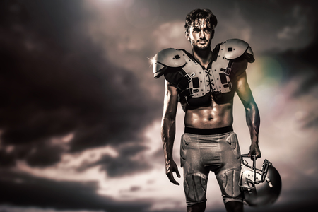 padding: Shirtless American football player with padding holding helmet against blue and orange sky with clouds