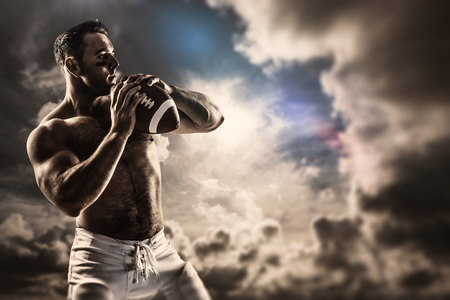 Shirtless American football player with ball against dark sky with white clouds