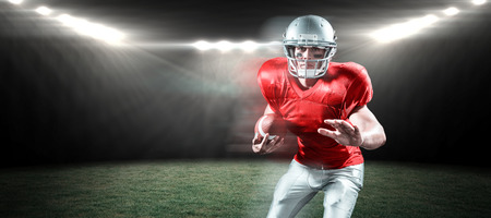 Portrait of defensive sportsman holding American football against rugby stadium