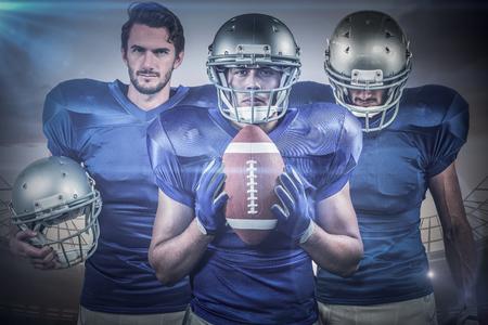 blue lights: American football team against large football stadium under cloudy blue sky