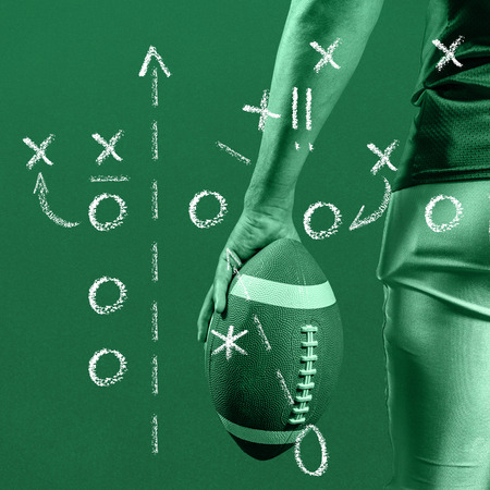 cropped: Cropped image of American football player holding ball against green Stock Photo