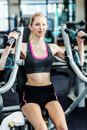 exercise machine: Fit woman using exercise machine  against fitness interface Stock Photo