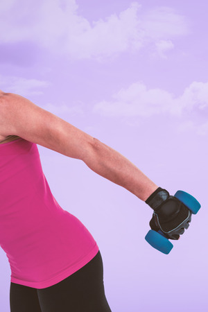weightlifting gloves: Muscular woman exercising with dumbbells  against purple background