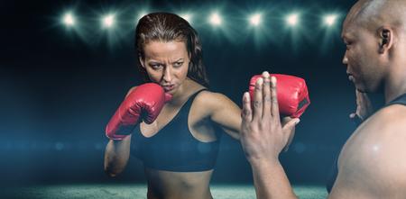 female boxer: Female boxer practicing with trainer against desert landscape