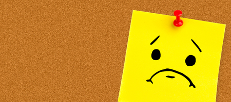 yellow pushpin: Angry face against illustrative image of pushpin on yellow paper Stock Photo