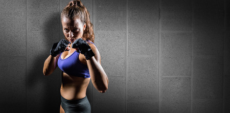 Portrait of woman with fighting stance against dark grey room Stock Photo
